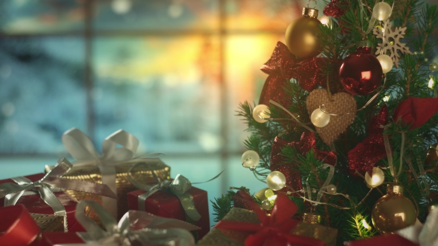 New Years Christmas background with frosty window and falling snow on the background. Christmas tree, gifts. Decorations, red gold balls, glowing bulbs. Warm home mood. Depth of field. Red camera 4K Royalty-Free Stock Footage #1062545683