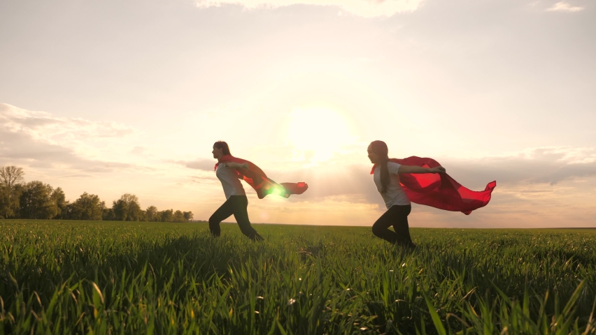 Happy girls play superheroes they run across green field in red cloak, cloak flutters in wind. children's games and dreams. Slow motion. teenager dreams of becoming superhero. young girls in red cloak | Shutterstock HD Video #1062550918