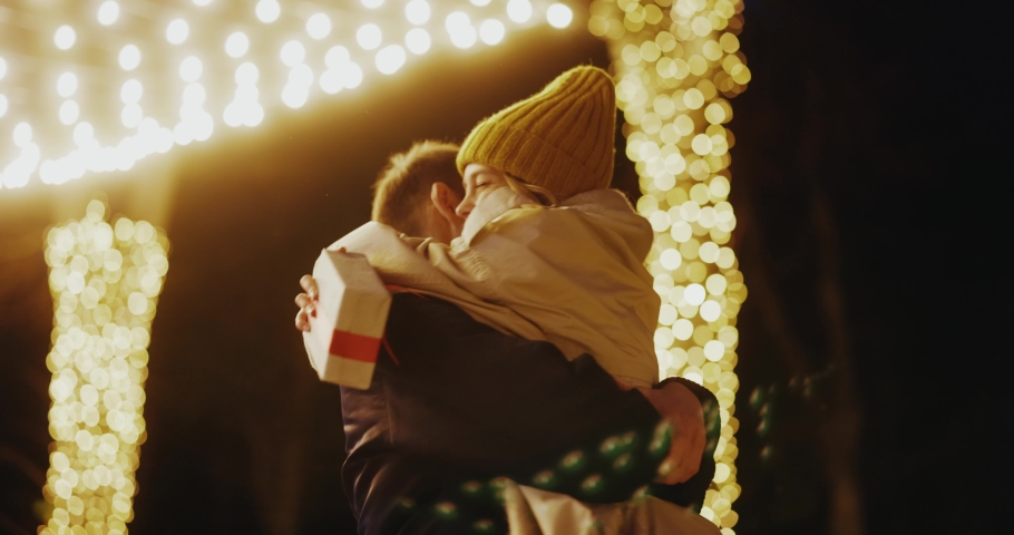 Young woman meeting up with boyfriend on birthday christmas evening party hugging tightly together swinging on the street. Illumination. Beautiful love couple. Royalty-Free Stock Footage #1062557854