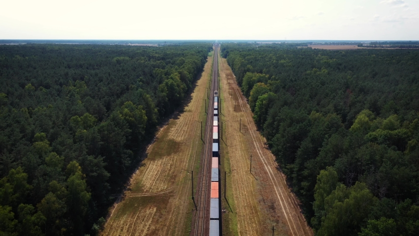 Electric locomotive with freight cars or railway wagon rides on railroad. Transportation and delivery of cargo in containers between cities and countries. Aerial view over train riding through forest