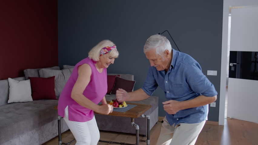 Happy old senior couple dancing celebrating retirement anniversary in modern living room at home. Grandmother and grandfather having fun dance enjoying relationship milestone celebration. 6k downscale | Shutterstock HD Video #1062566863