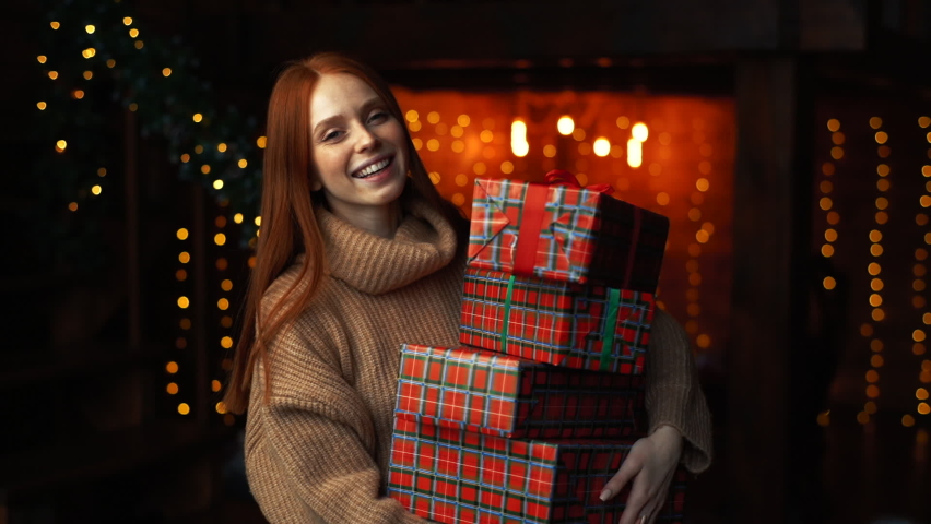 Happy young woman holding many beautiful Christmas gift boxes on background of xmas lights at cozy dark room. Cheerful lady drops box with gift, tries to catch and looks at camera enthusiastically. | Shutterstock HD Video #1062571846