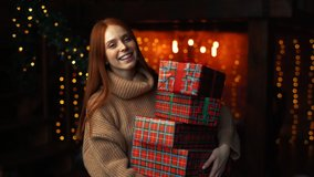 Happy young woman holding many beautiful Christmas gift boxes on background of xmas lights at cozy dark room. Cheerful lady drops box with gift, tries to catch and looks at camera enthusiastically.