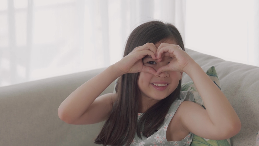 Young mixed Asian girl making heart shape gesture with her hands over her eyes , Happy volunteer ,donation and charity, love, heart health concept Royalty-Free Stock Footage #1062575611