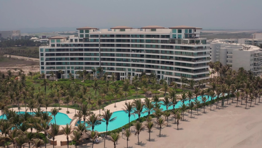 Aerial View on Upscale Condo Buildings and Pools By Tropical Beach in Acapulco, Mexico