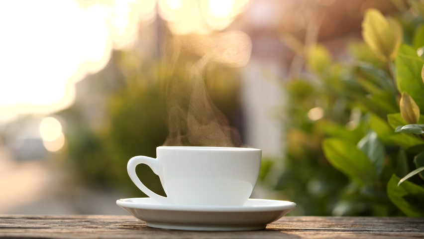 Close-up steaming hot coffee or tea cup on saucer, slow motion. Hot ceramic white coffee cup with smoke on old wooden table in nature background. Hot Coffee Drink Concept