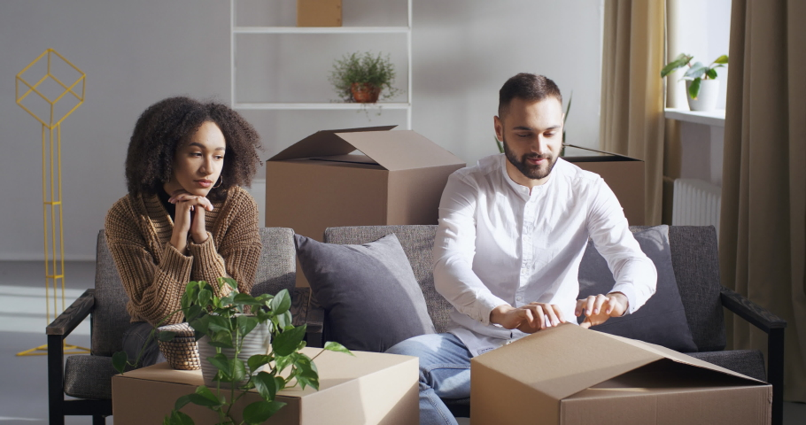 Multiethnic couple african american girl and caucasian man sitting together on sofa in room in new house, moving to apartment, sorting out boxes of things, receiving parcel, guy giving his wife gift Royalty-Free Stock Footage #1062612199
