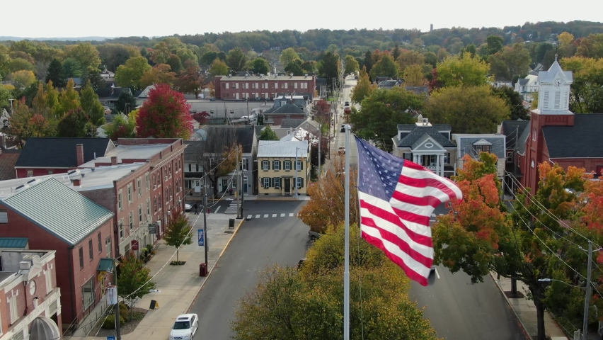 Patriotic American Flag flies over town square in Anytown USA. Beautiful cinematic aerial shot.