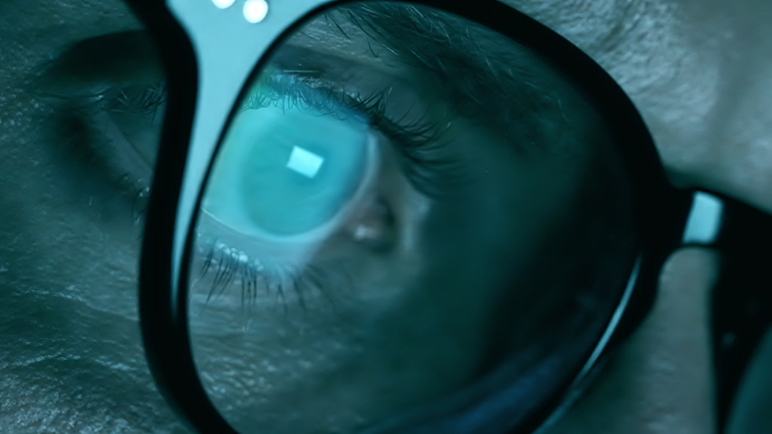 A close-up view into the eye of a computer hacker as he monitors a computer screen in real-time. | Shutterstock HD Video #1062621421