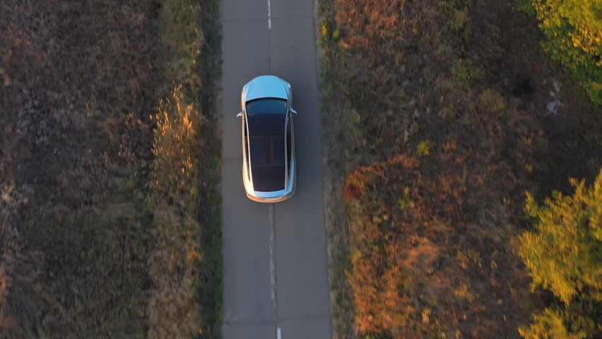 Aerial shot of electrical car driving through country road at summer evening. Modern vehicle passing rural highway. Ecology friendly car riding on electric charge along motorway. Top view Royalty-Free Stock Footage #1062622180