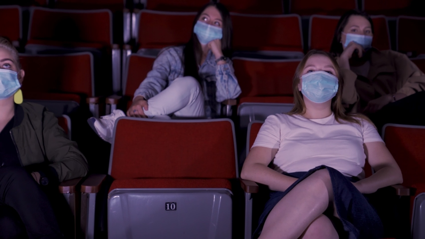 Cinema, entertainment, pandemic, and social distance concept. Media. People wearing face protective medical masks for prevention of virus disease watching movie in theater. Royalty-Free Stock Footage #1062628711