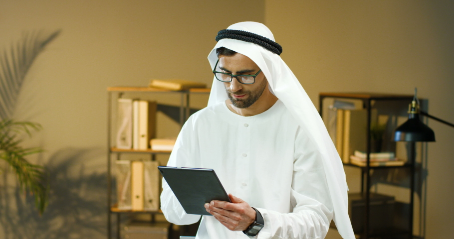 Arabic handsome man in glasses and Kandura standing in office, tapping and scrolling on tablet device screen. Muslim businessman in traditional emirates clothes. Arab male using computer. UAE business