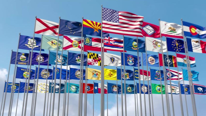 All the Flags of the United States together on a flagpole flutter in the wind. The camera slowly moves away from the flags and zooms to the wide shot.