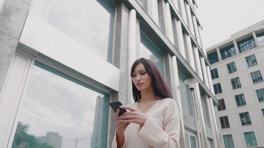 Young beautiful businesswoman using smartphone and walking on city streets of downtown. Business female commute browsing social media happy lifestyle outdoors.