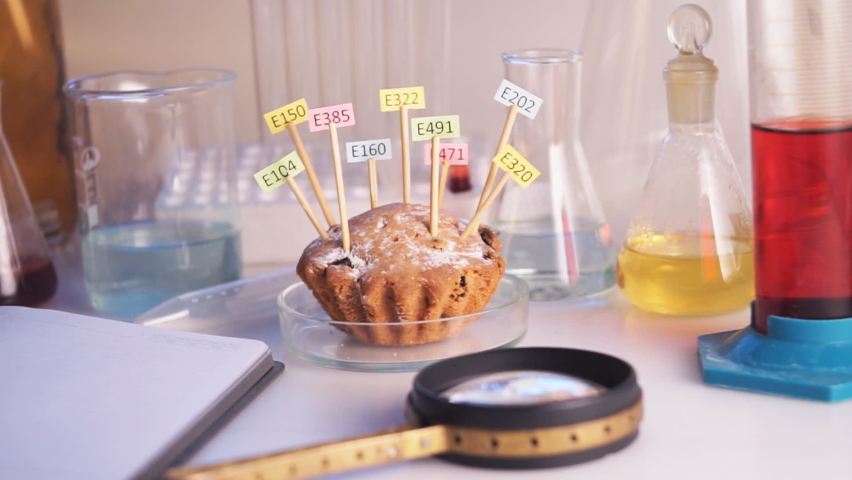 Healthy eating concept. The hand of the laboratory assistant is holding a magnifier in his hands, the cupcake on the table is decorated with tablets with the names of the additives of E. Food | Shutterstock HD Video #1062646567