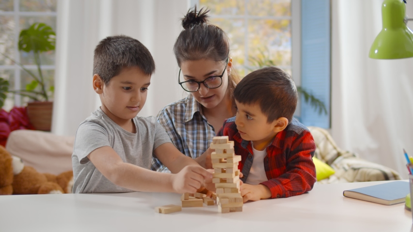Happy young mother and two little children sitting at table and playing together. Nanny playing board game with preschool boys building tower with wooden bricks Royalty-Free Stock Footage #1062651478