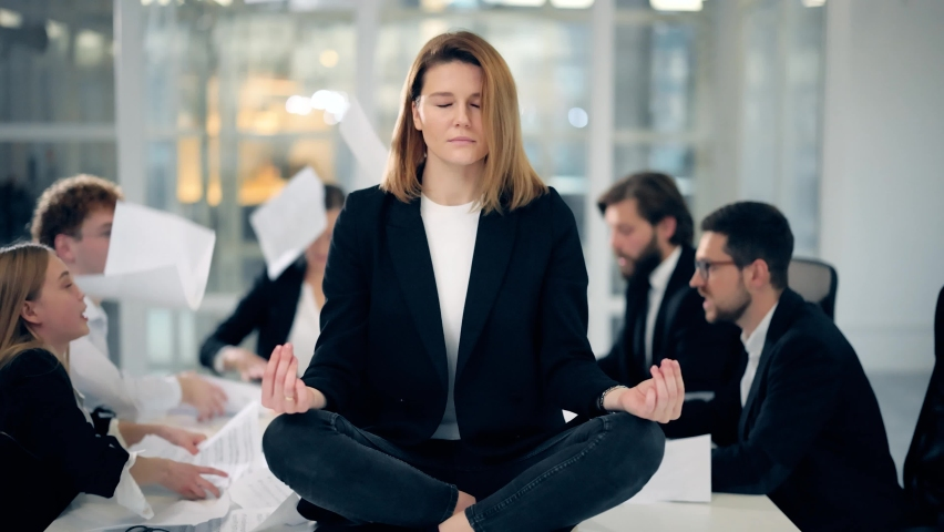 Calm blonde business woman dressed in classic black suit meditate in lotus position while office workers arguing and throwing papers to each other faces on business meeting at the background | Shutterstock HD Video #1062660502