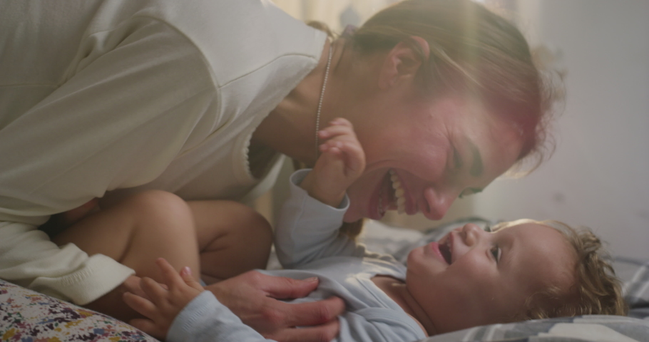 Cinematic close up shot of young happy mother is tickling and playing with her toddler baby boy in a nursery woke up in a morning. Concept of love, parenthood, childhood, life, maternity, motherhood.