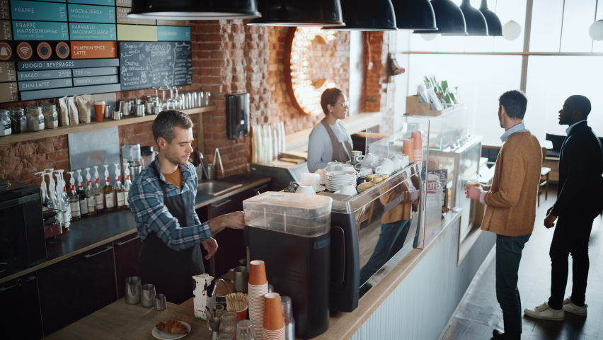 Latin Female Cashier and Male Barista in Checkered Shirt Accept Orders from Diverse Clients in Coffee Shop Bar. African American Handsome Customer Orders Take Away Latte from a Cozy Lifestyle Cafe. Royalty-Free Stock Footage #1062664309