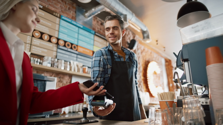 Female Customer Pays for Take Away Coffee with Contactless NFC Payment Technology on Smartphone to a Handsome Barista in Checkered Shirt in Cafe. Customer Uses Mobile to Pay Through Bank Terminal.