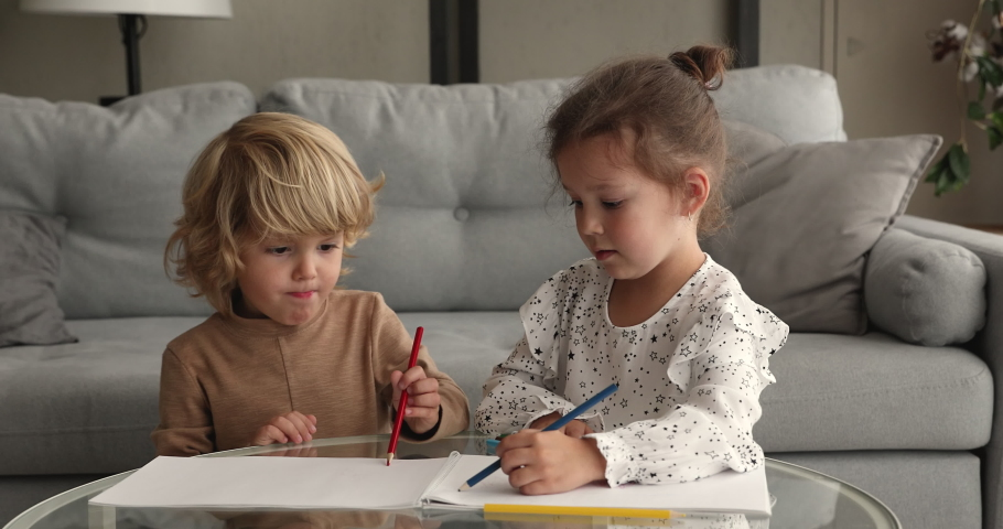 Little siblings sitting in living room at table drawing together pictures in sketchbook. Older friendly sister teaching to younger brother paint with pencils showing care. Friendship, hobby concept Royalty-Free Stock Footage #1062671260