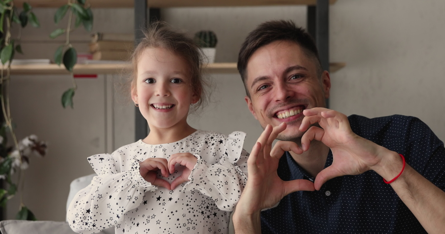 Young father and little 5s adorable daughter smiling looking at camera showing symbol making with fingers heart shape sign of love. Concept of blood donation and save life, volunteering, family bond