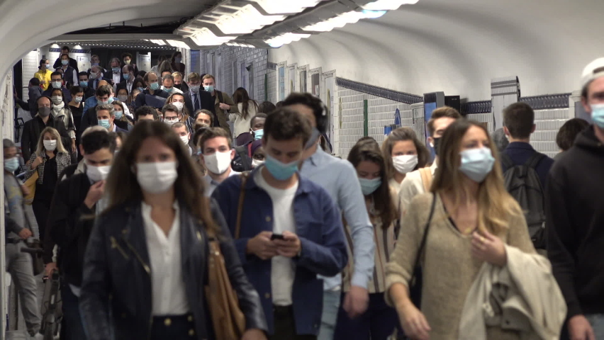 PARIS, FRANCE – SEPTEMBER 2020: Covid-19 coronavirus global pandemic. Commuting railway passengers wearing protective face masks walk through busy corridor in metro system of Paris, public transport
