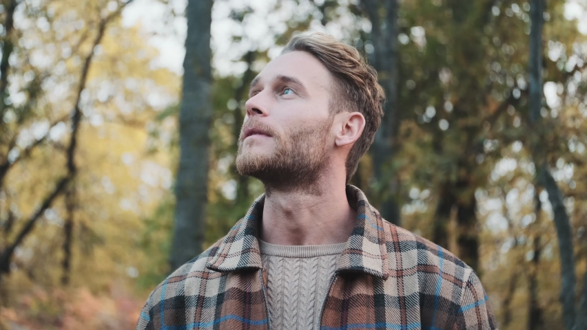 A smiling man is looking around while walking outside in the autumn park | Shutterstock HD Video #1062677080