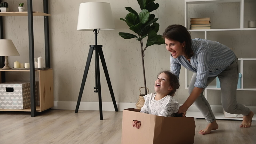 Young mom and small daughter play crazy creative games at home, mother barefoot run ride cute kid girl while she sit inside of big carton box, family fool around enjoy playtime at new modern warm flat | Shutterstock HD Video #1062680134