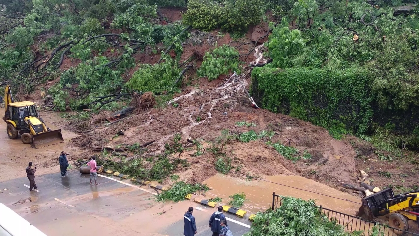 MUMBAI/INDIA- AUGUST 6, 2020: Emergency services work to clean clear and vegetation from a road following a landslide at Padder road after recent heavy monsoon rains.