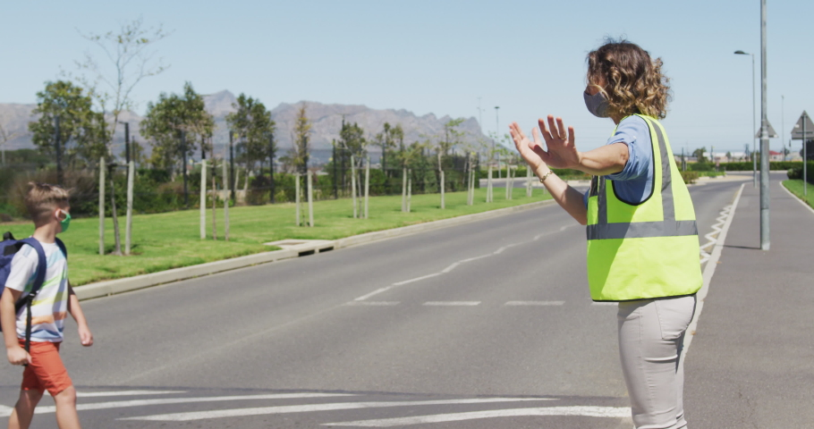 Female teacher in a face mask and high visibility vest stops traffic on a pedestrian crossing so children wearing face masks can cross the road safely. road safety back to school covid19 coronavirus. Royalty-Free Stock Footage #1062689806