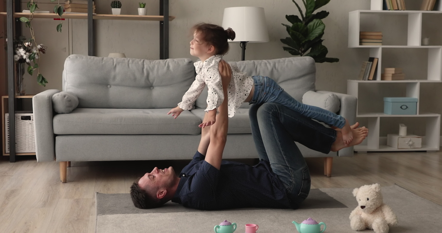Father lying on carpet on warm floor lifts up little cute daughter she spread arms looking like plane wings, happy family dreaming about travel and vacation. Fun and leisure with kid at home concept Royalty-Free Stock Footage #1062694636