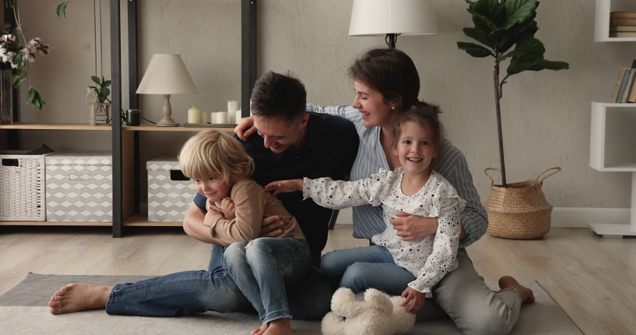 Happy married couple play with little kids tickling them having fun sit on warm floor in modern living room. Homeowners family, bank loan, tenant, playtime at quarantine with son and daughter concept