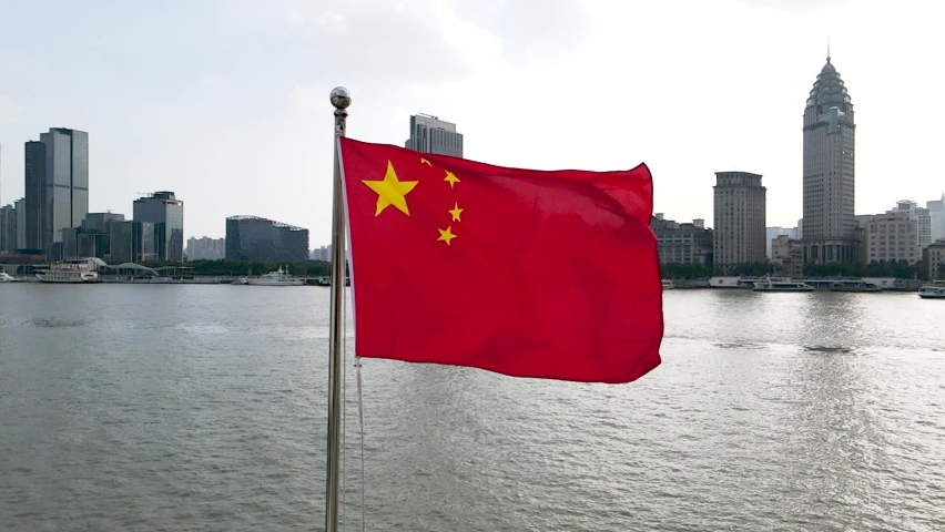 Chinese National Flag blowing around famous landmark, the Bund, in downtown Finance business Chinese culture concept b roll footage China's 5 star national flag in the wind in downtown Shanghai China Royalty-Free Stock Footage #1062696361