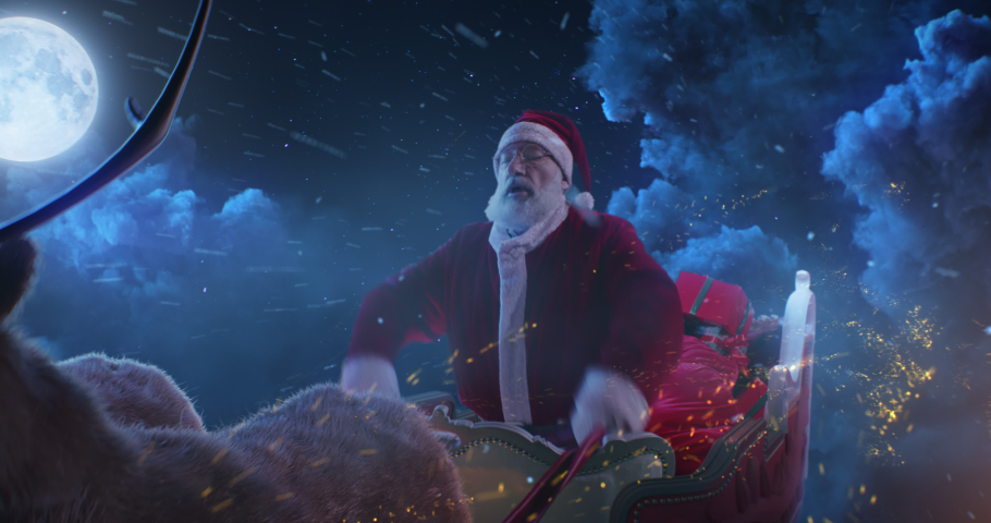 Senior man in Santa Claus costume grasping reins and urging reindeer forward then stopping sled against clouds and moon in night sky on Christmas eve