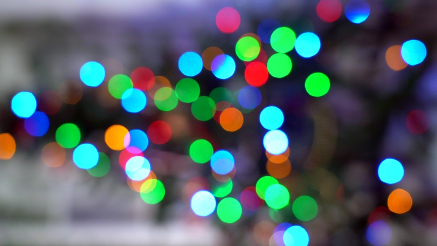 Blurred silhouette of Christmas tree with lights glowing Out of focus. Vertical 4k video. Christmas tree in interior with defocused lights. Christmas blur background. Light bokeh from Xmas tree.  | Shutterstock HD Video #1062705631
