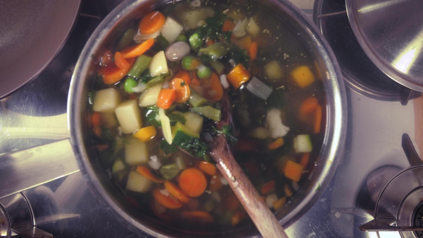 Stirring a pot of vegetable soup top view. Minestrone soup boiling in the pot. Vegetarian healthy meal for dinner. Ready vegetable meal for lunch, hot and cozy soup for dinner at home