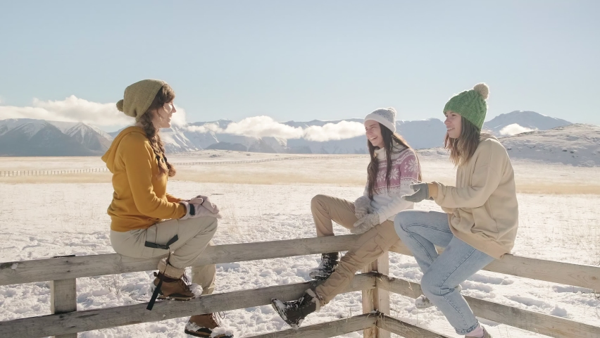 Three women in sweaters and hats with pompoms sit on a wooden fence, chatting and laughing. First snow in the mountains Royalty-Free Stock Footage #1062706327