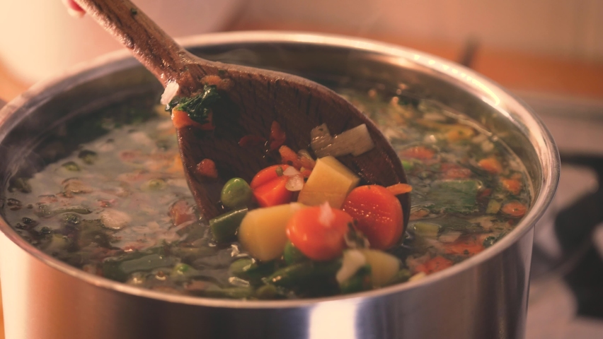 Stirring a pot of vegetable soup close up. Minestrone soup boiling in the pot. Vegetarian healthy meal for dinner. Ready vegetable meal for lunch, hot and cozy soup for dinner at home