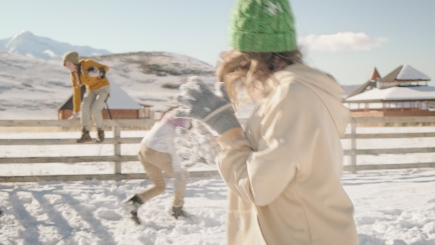 Three cheerful women in sweaters and pom-pom hats are having fun and playing snowballs. First snow in a valley in the mountains Royalty-Free Stock Footage #1062707539