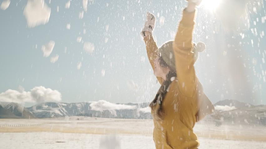 A playful young woman throws snow up and circles around her in front of the mountains. First Snow Concept Royalty-Free Stock Footage #1062707863
