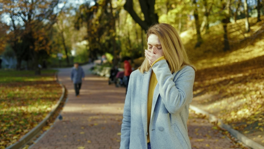 Attractive young woman having headache feel unhappy stand in autumn park at sunlight. Blonde stressed lady. Portrait pain tired. Sick. Close up. Slow motion