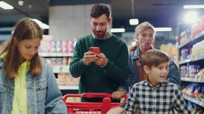 Busy father businessman using smartphone on shopping with family. Mother young woman arguing with husband about mobile phone addiction. Supermarket. Conflict.