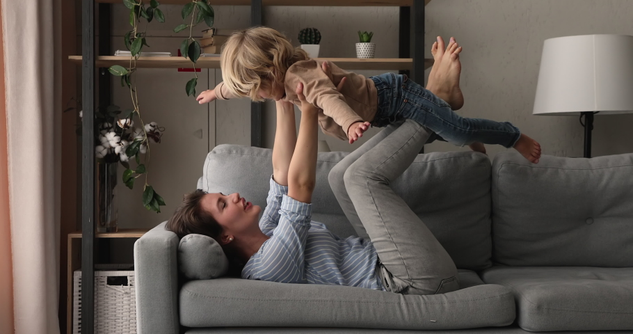 Loving young mom lying on couch play with preschool son imitate plane fly in air, happy mother relax have fun with little boy, enjoy family active weekend together at home, games and leisure concept   Shutterstock HD Video #1062711127