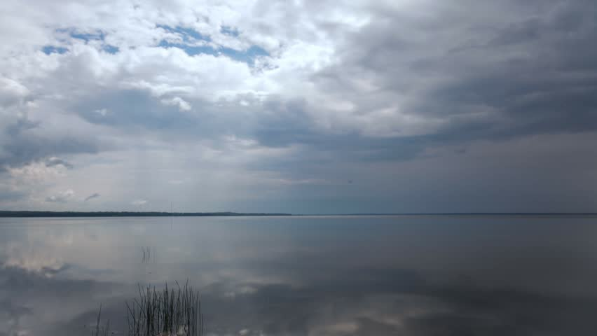 Time-lapse of clouds flying over calm lake, wide angle shot | Shutterstock HD Video #10627115