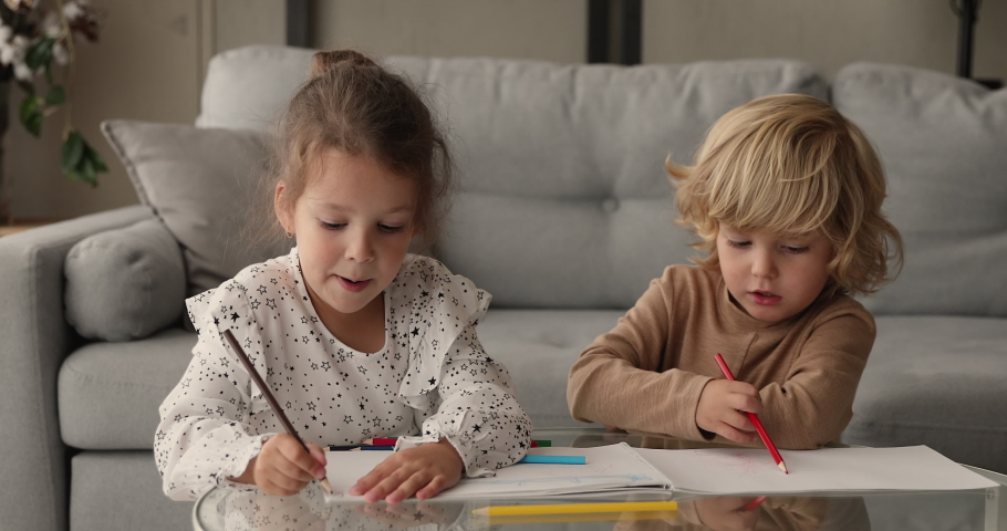 Two little friends siblings spend free time at home drawing with colorful pencils in sketchbook chatting enjoy common hobby and leisure activity. Kid development children education, friendship concept #1062718720