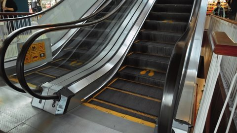 Black staircase escalator in a shopping center with a footprint sign for keeping a social distance