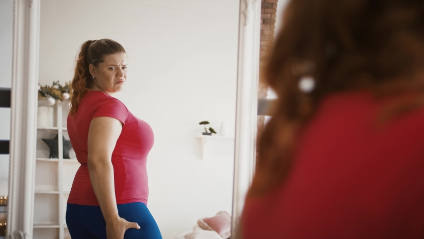Body weight problem. Depressed lady with excess weight looking at mirror, feeling stressed about her figure and obesity Royalty-Free Stock Footage #1062728413