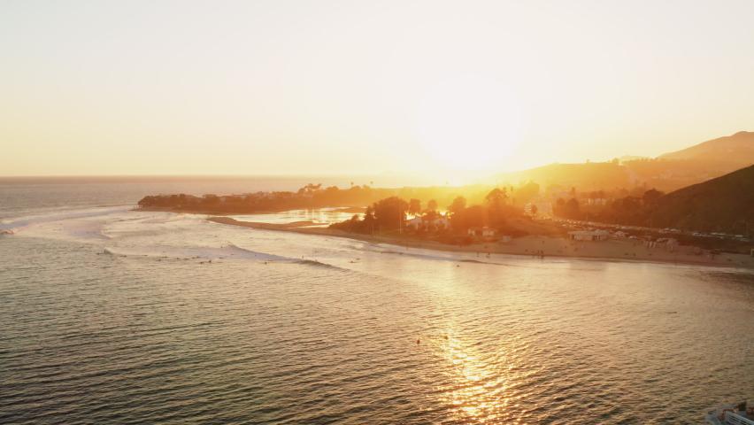 Surfers catching waves in Malibu by the Malibu pier at sunset. Surfing hobby, Malibu Lifestyle