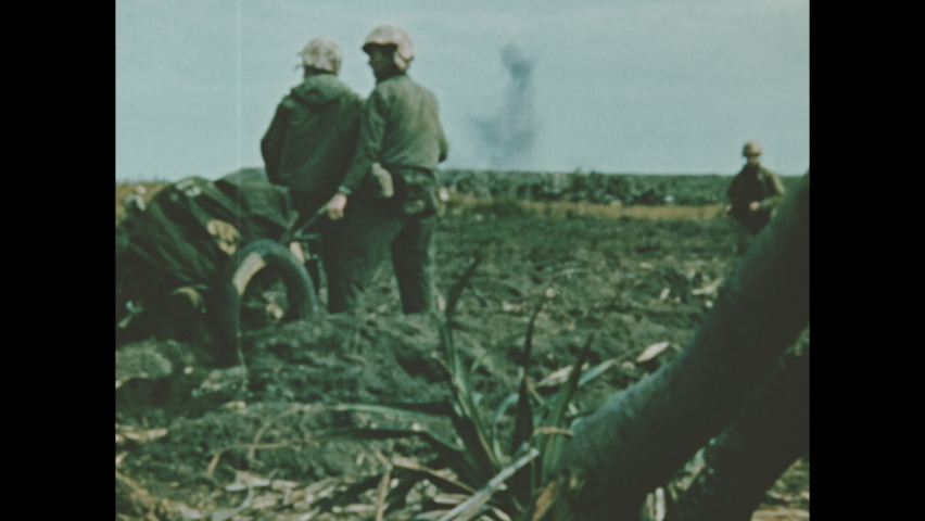 1940s Iwo Jima: Plants wave near mountain on Iwo Jima. Soldiers drag wheeled cart across muddy battlefield. Soldiers walk and sit among tall grass. | Shutterstock HD Video #1062733732